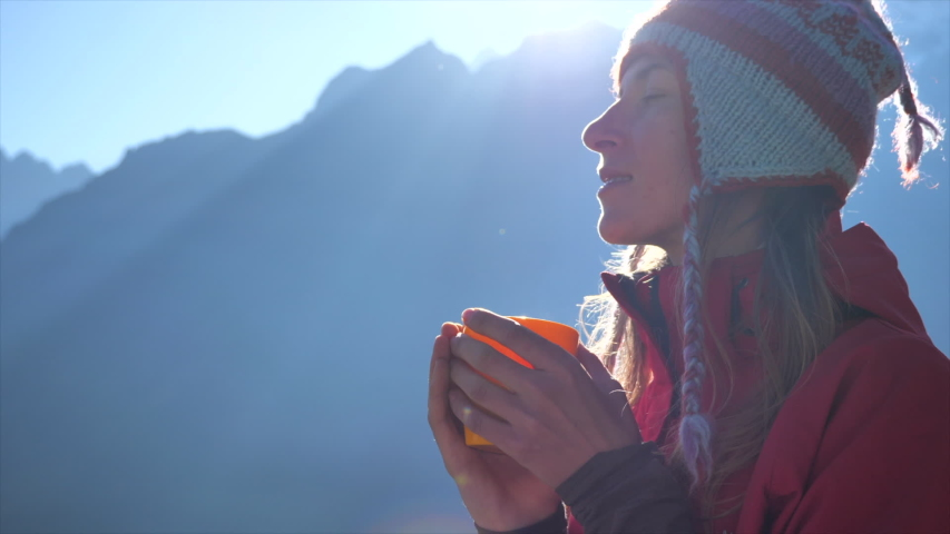 Woman drinking a hot drink, enjoy the view of  Himalayan mountains in Nepal   Shutterstock HD Video #1053655772