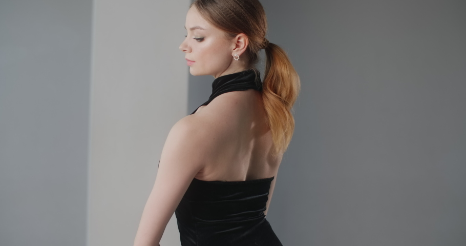 Attractive young woman dancer in black dress with open back rehearses dance moves, ballet rehearsal, ballerina does dance steps in the stage costume, dance studio lesson, 4k 60p Prores HQ   Shutterstock HD Video #1053657374