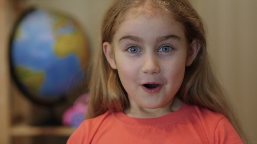 Portrait Little Girl With Blue Eyes Looking at Camera. Closeup. Portrait of Young Child Surprised and Shocked. Slow motion. Girl Looks and is Surprised and Happy to Receive Surprise. Close Up.    Shutterstock HD Video #1053658403