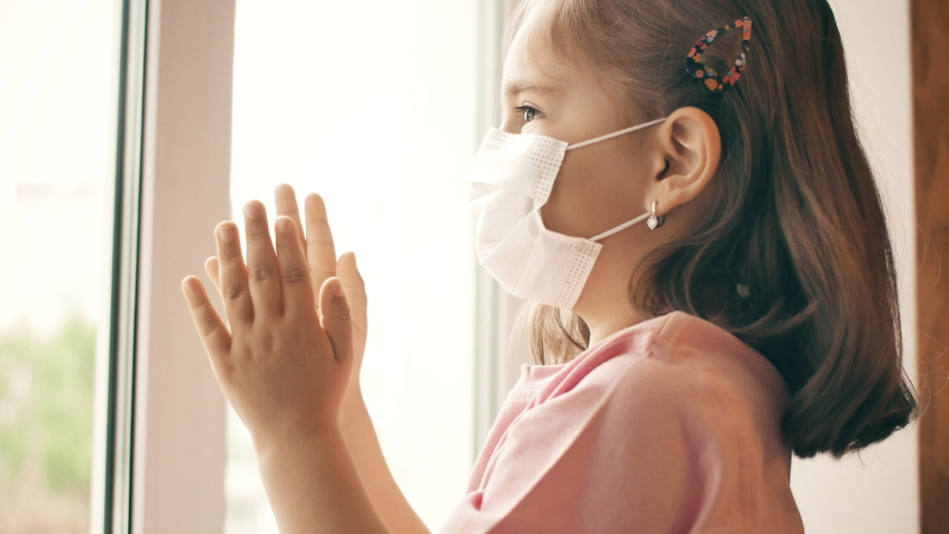 Little girl in medical mask looks through the window during worldwide virus epidemic. The girl is applauding for health workers. Celebration quarantine ending. Coronavirus COVID-19 infection concept Royalty-Free Stock Footage #1053661238