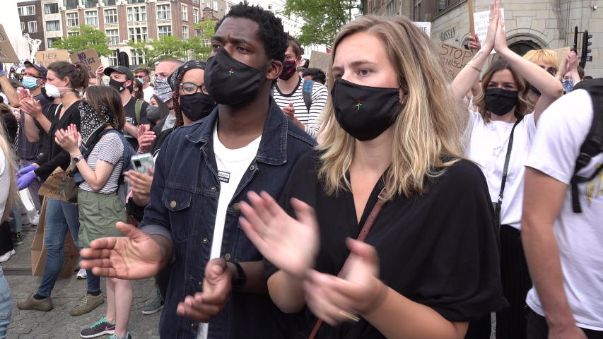 AMSTERDAM, NETHERLANDS – 1 JUNE 2020: Mixed race couple in Amsterdam protests against police violence and racism in support of demonstrations in the US. Covid-19 coronavirus pandemic face masks.