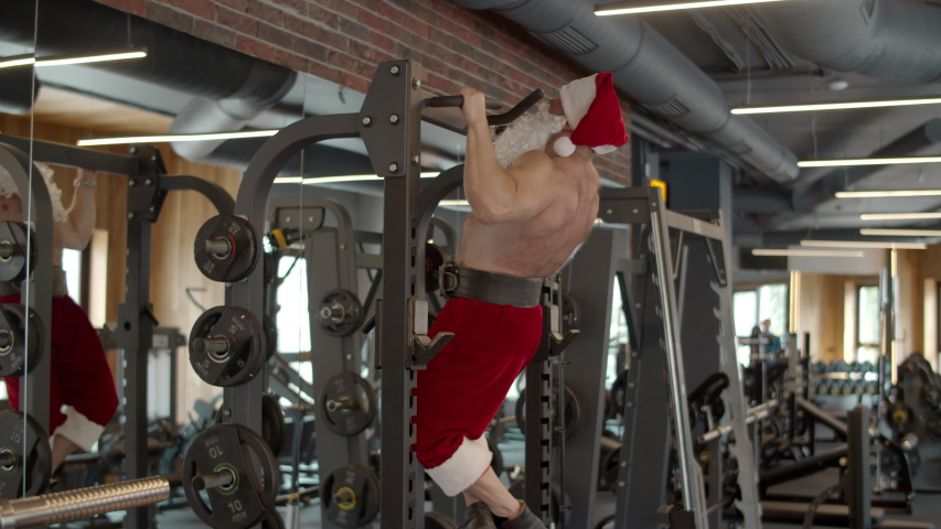 Closeup strong santa man doing pullups at gym. Serious bodybuilding man in christmas hat making exercises in sport club. Ambitious male athlete in santa costume workout in fitness center. | Shutterstock HD Video #1053670160