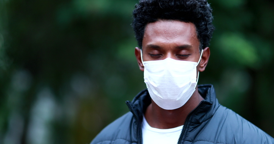 Portrait black African man wearing surgical face mask prevention against outbreak pandemic opening eyes   Shutterstock HD Video #1053673460