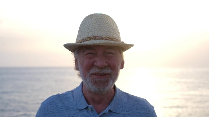 Close up and portrait of mature man or senior smiling laughing and looking at the camera - happy active and healthy lifestyle or pensioner - ocean or sea in the background with sunset | Shutterstock HD Video #1053674246