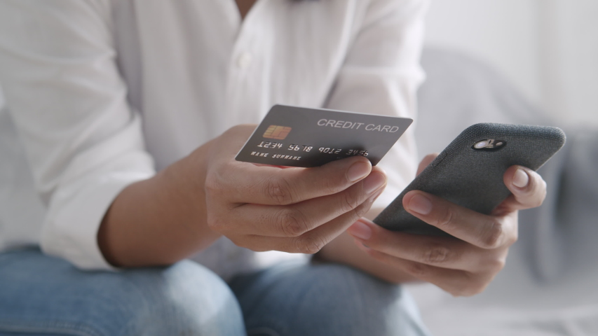 Side view. Hand of young women are buying online with a credit card. woman are using smartphone and doing online transactions at home. Concept of shopping online by technology and lifestyle new normal Royalty-Free Stock Footage #1053684614