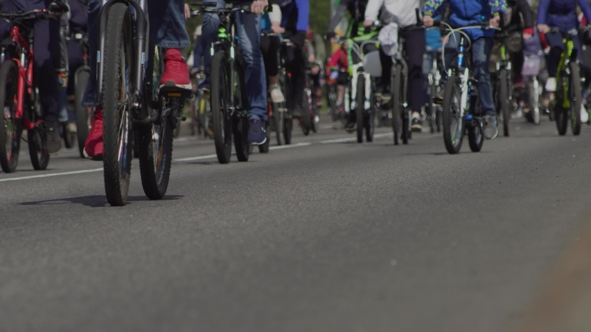 Mass bike rides in city. Bicycle marathon. Race competition event for cyclists. Citizens with their bicycles on main street. Column of athletes. Low angle shot of wheels | Shutterstock HD Video #1053685052