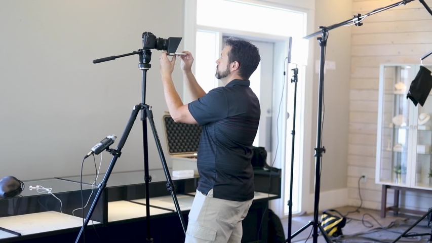 Videographer Setting Up Teleprompter. A lot of tripods and cameraman is adjusting teleprompter to the lens of the camera.  | Shutterstock HD Video #1053691001