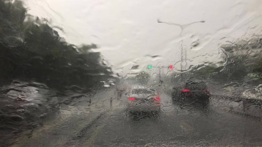 Road view traffic Bangkok through car window with heavy rain drops driving in rain.Traffic view from car windscreen in rain.Driving in rain.