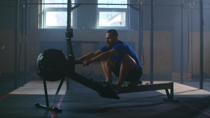 Slow motion: one man in an atmospheric fitness room in the sun in a rowing machine | Shutterstock HD Video #1053705092