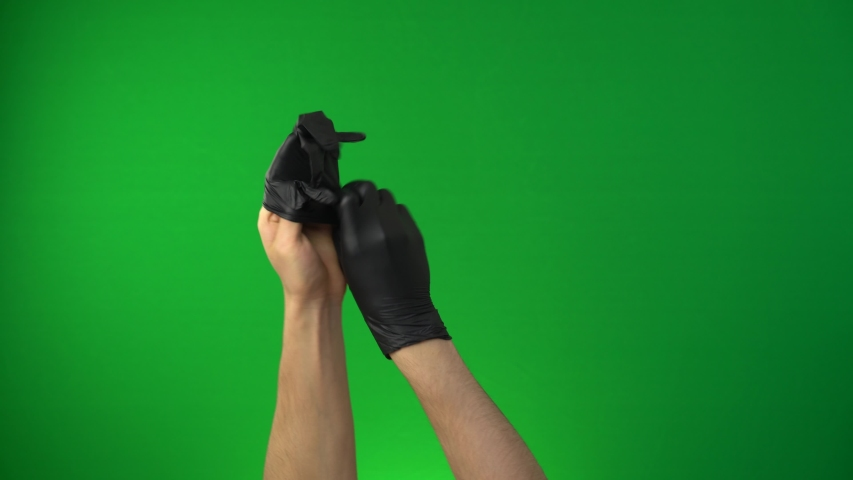 Man puts on gloves. Coronavirus pandemic, Covid-19. Hands in a black medical glove isolated on a chroma key green screen background | Shutterstock HD Video #1053705275