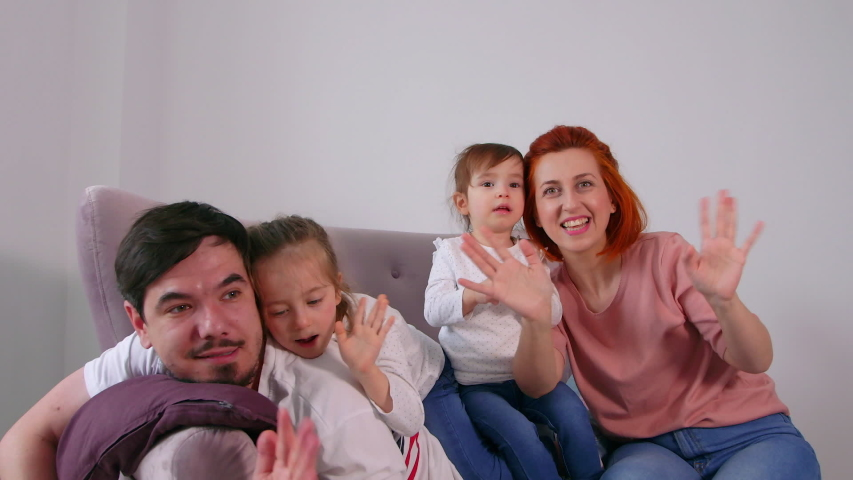 Excited happy adult parents mom dad playing with cute little kids on sofa into new home concept #1053708680
