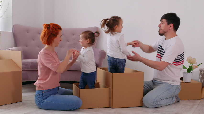 Funny active family playing on moving day, excited happy adult parents mom dad playing with cardboard boxes with cute little kids sit inside having fun packing relocate into new home concept #1053708686