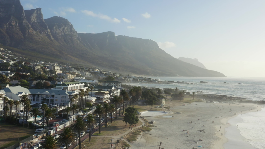 Wide aerial sweeping shot of Camps Bay blue flag beach, with views to the twelve apostles mountains, Cape Town, South Africa