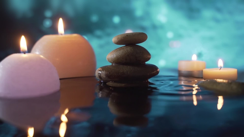 Burning candles in water, reflection of stones on abstract blue background, water drops falling. slow motion. Close up. Concept: relaxation, wellness, body care, spa, nature, aromatherapy and scents   Shutterstock HD Video #1053716828