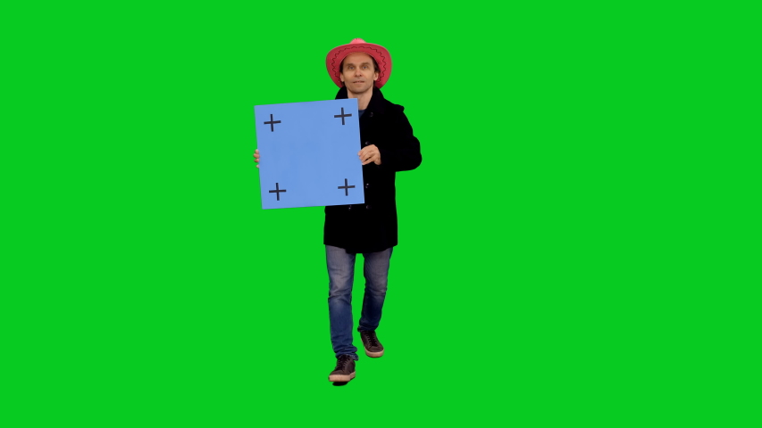 Stylish handsome man in pink cowboy hat holding blue blank board while walking and speaking on green screen background, Chroma key 4k pre-keyed footage
