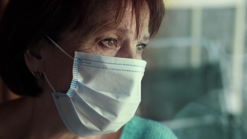 Elderly woman in face mask behind window Royalty-Free Stock Footage #1053727241