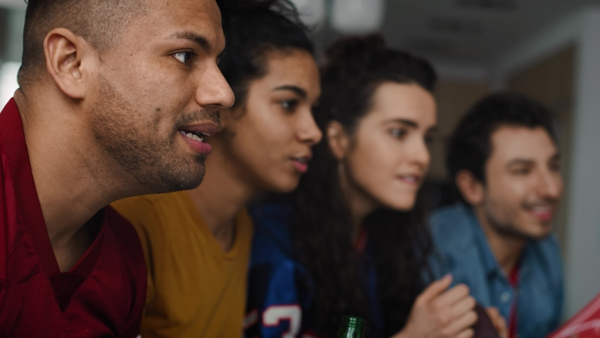 Side view video of friends watching Tv and cheering together. Shot with RED helium camera in 8K | Shutterstock HD Video #1053730058