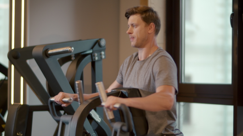 Strong bodybuilding man making bicep curls in sport club. Closeup aggressive fitness man doing repetitions in fitness center. Portrait of attractive male athlete training at gym. | Shutterstock HD Video #1053731993