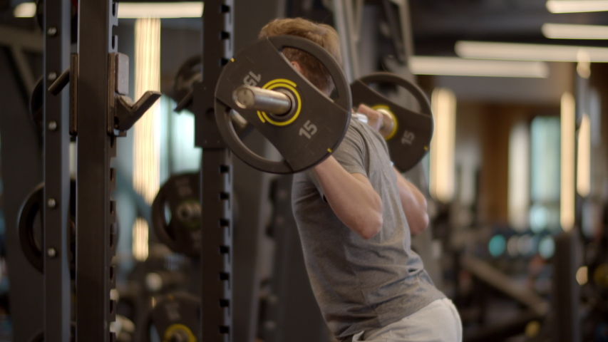 Closeup young bodybuilding man doing barbell squats at gym. Confident sportsman making repetitions in sport club. Sporty fitness man training in fitness center. | Shutterstock HD Video #1053732032
