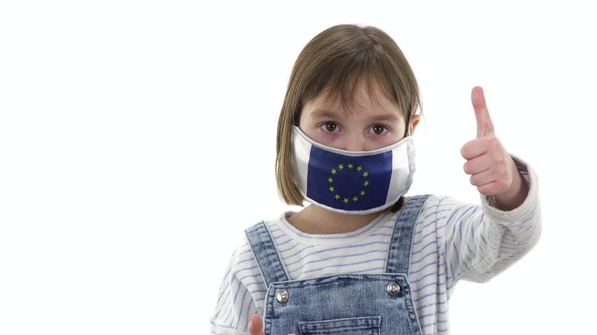 Charming girl, blonde posing on a white background. Quarantine, virus and pandemic concept. On the child a protective medical mask with the flag of the European Union. Different emotions and gestures. | Shutterstock HD Video #1053734255