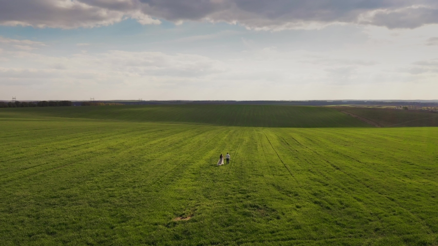 Aerial view 4k. a pregnant girl in a long dress and a guy walk along a huge green field. like a window saver. On the Sunset. the sun's rays break through the clouds | Shutterstock HD Video #1053736094