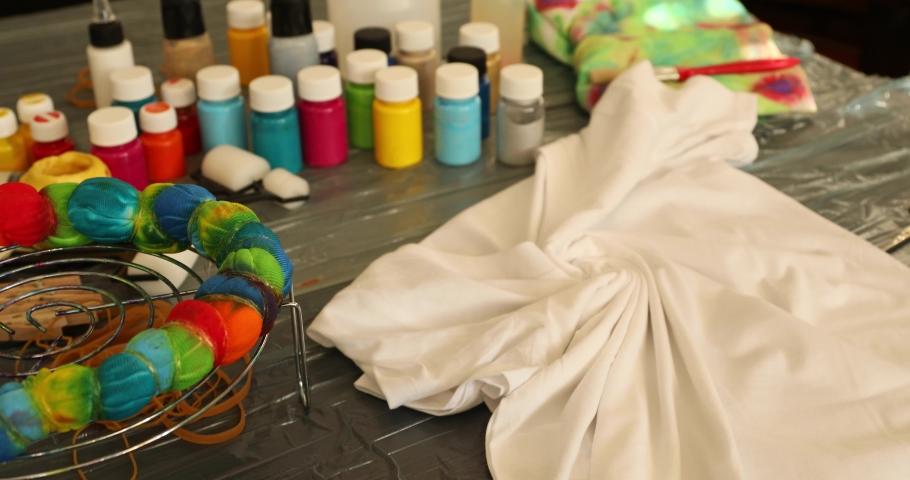 Woman applying tie dye technique to t shirt   Shutterstock HD Video #1053736190