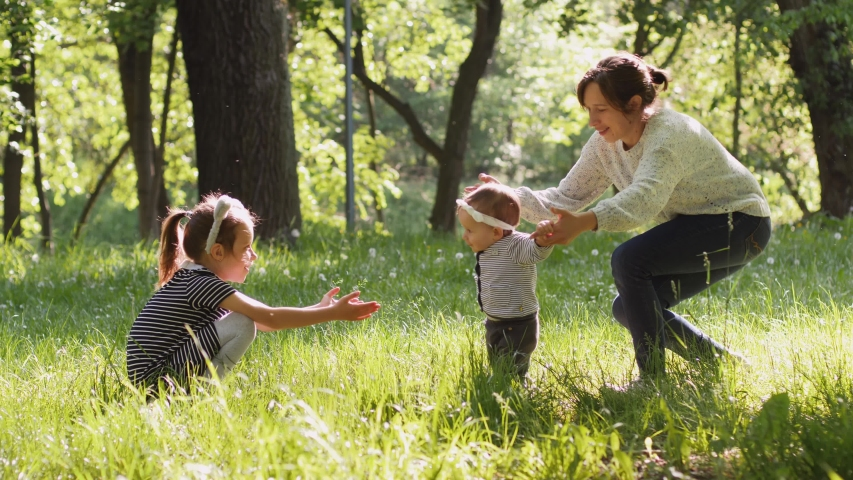 Mother and elder sister spin and walk with baby toddler making first steps on park grass happy family girls play together on nature