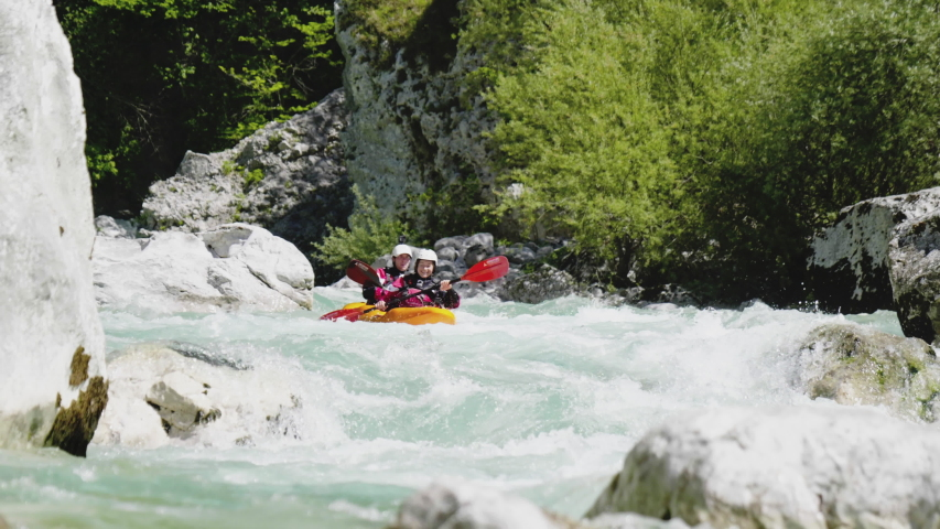 Slow motion close up two people kayaking in dual kayak on emerald whitewater river, over rapids, enjoying nature Soca, Slovenia | Shutterstock HD Video #1053752450