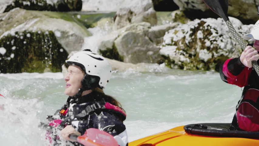 Slow motion close up two people kayaking in dual kayak on emerald whitewater river, over rapids, enjoying nature, Soca, Slovenia