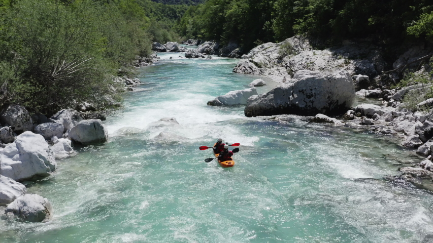 Aerial follow cam shot of dual kayak going down the emerald alpine river Soca, Slovenia