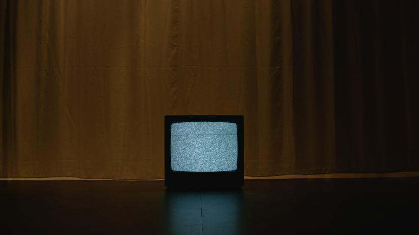 Old CRT TV is on the floor in a dark and empty room. On the screen there is a frightening white noise filling the room with a hypnotizing atmosphere of mystical evil. Dolly camera movement