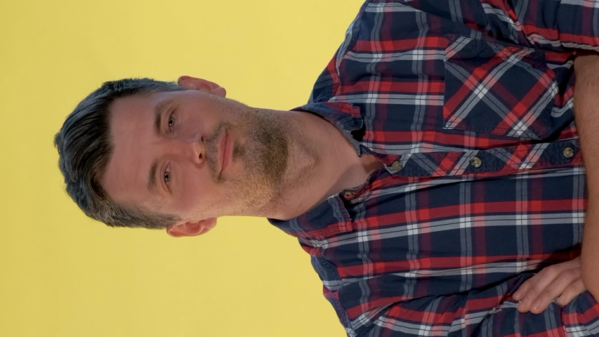 Close up of young man making a hush gesture on yellow background. It must be quite there. Video with Vertical Screen Orientation 9:16   Shutterstock HD Video #1053758465