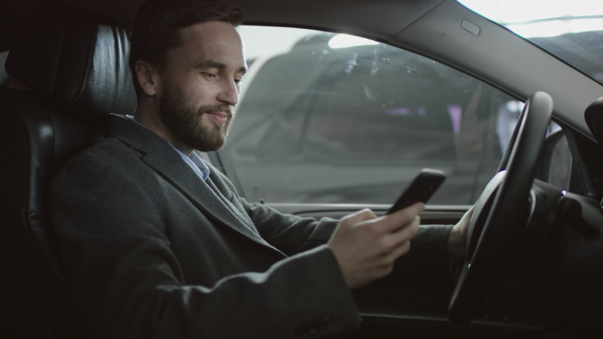 Surfing the internet happy handsome man sitting in the car on a driver's seat and using his phone. Businessman reding news while sitting in a car.