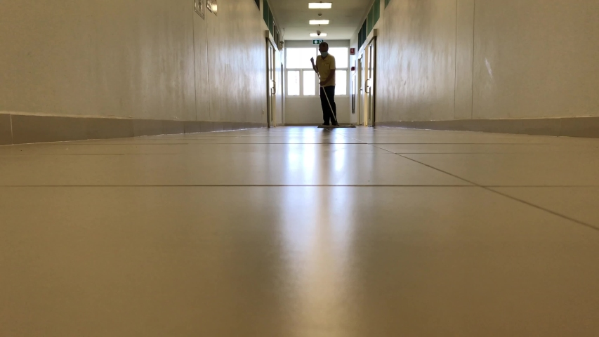 Janitor man mopping floor in hallway office building or walkway after school and classroom work job footage. | Shutterstock HD Video #1053759572