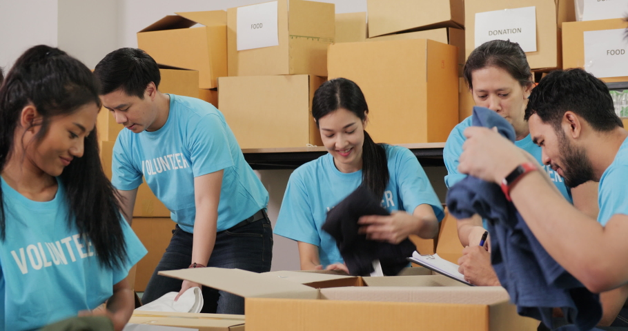Male and female volunteer preparing clothes for poor people during covid19. As charity workers and members of the community work together. Royalty-Free Stock Footage #1053762968