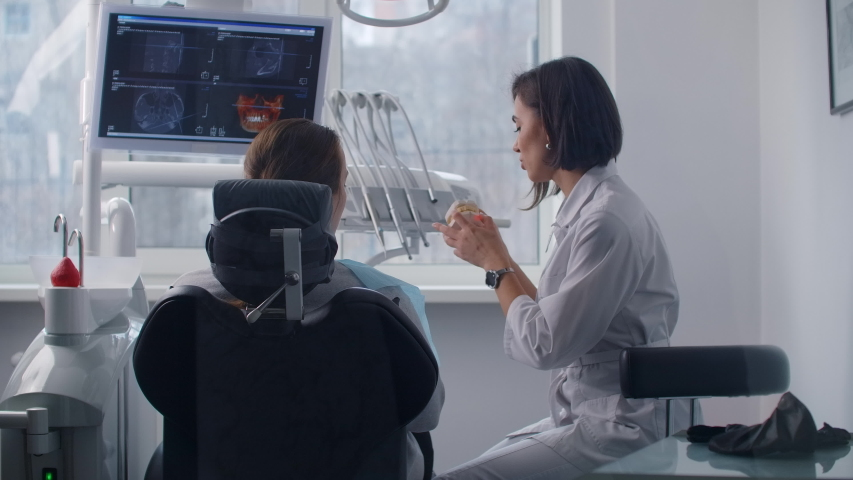 A female orthodontist dentist talks to a patient and shows problematic teeth on a cast discussing a treatment plan Royalty-Free Stock Footage #1053766937