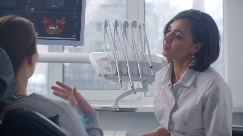 An orthodontist discusses an MRI scan with a patient sitting in a chair Royalty-Free Stock Footage #1053766952