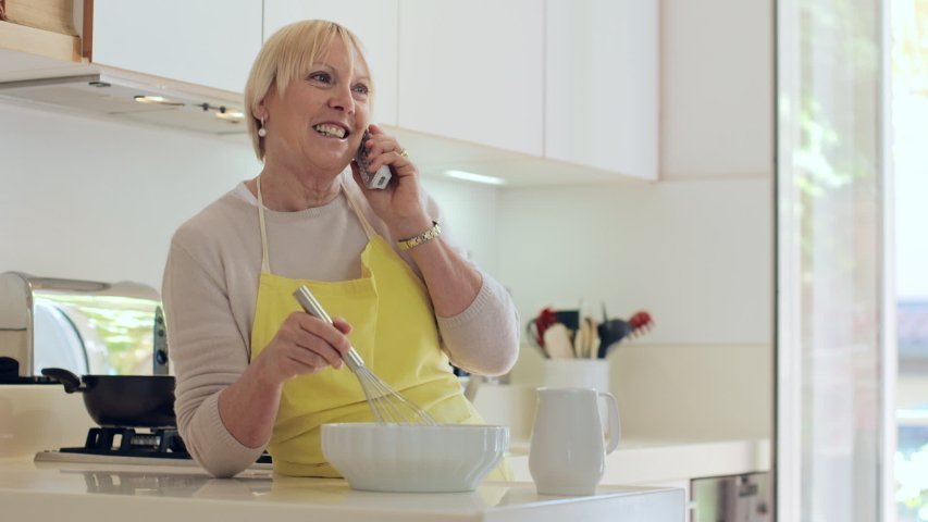 Happy active senior woman at home, cooking in kitchen and talking on the phone with friend. Old retired lady preparing food and speaking with telephone