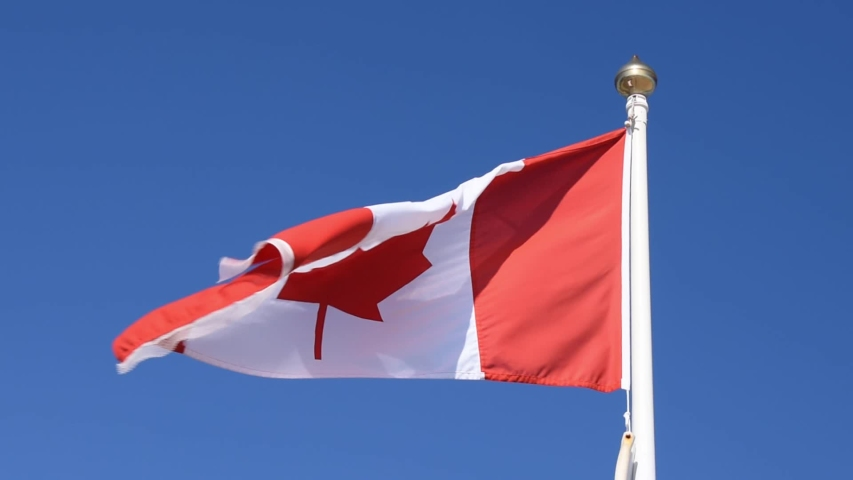 The National Flag of Canada also known as The Maple Leaf fluttering in the breeze.