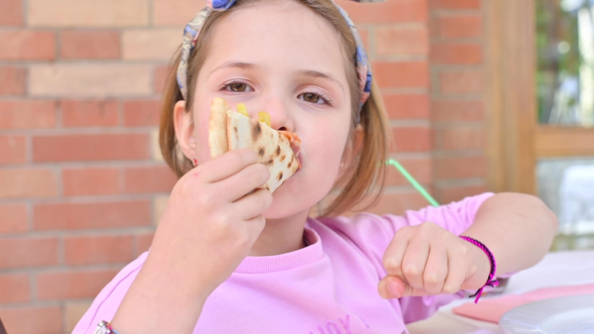 Little girl 7 years old eats pizza. The child shows positive emotions and pleasure when he dines with street food. Traditional italian pizza on thin crust. | Shutterstock HD Video #1053773000