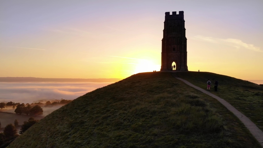 The golden sunrise appearing behind Glastonbury Tor and revealing the misty fields below.