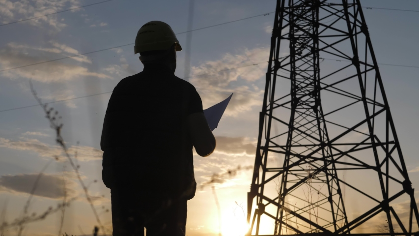 Silhouette of engineer standing on field with electricity towers. Electrical engineer with high voltage electricity pylon at sunset background. Power workers at work concept. | Shutterstock HD Video #1053775196