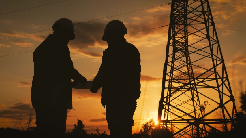 Silhouette of engineers looks at the construction of high-voltage power. Teams engineer looking discussing plan. Two engineer standing on field with electricity towers at sunset.