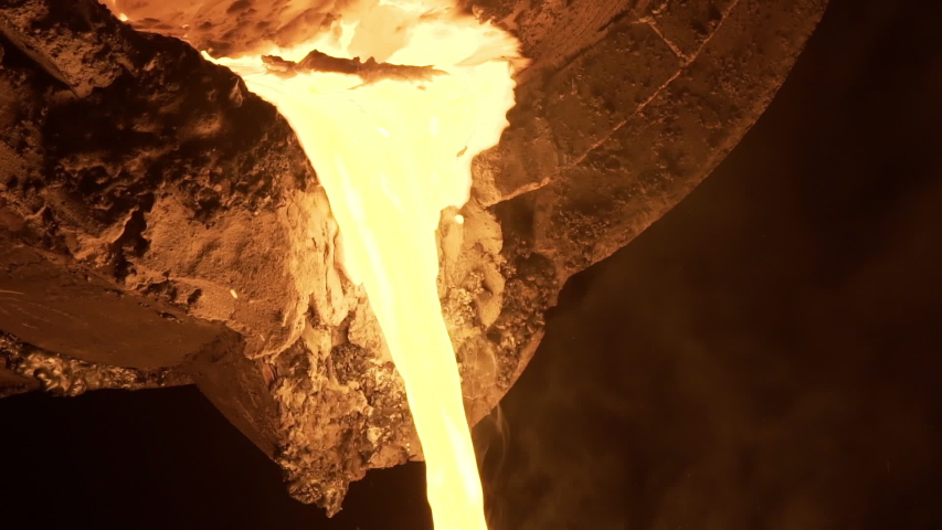 Stream of molten metal poured from one ladle to another in foundry. Liquid metal in furnace. Liquid metal production process. Molding molten metal at industrial plant. Slow motion