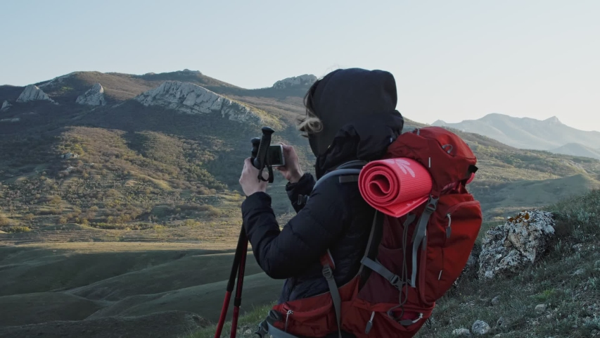 Woman in hike wear take a panorama shots on the mobile phone while standing on the slope of the mountain | Shutterstock HD Video #1053780800