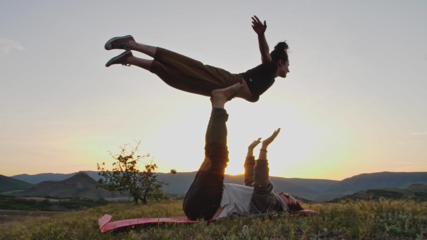 Couple practice complex exercises of yoga at dusk on the hilltop | Shutterstock HD Video #1053780818