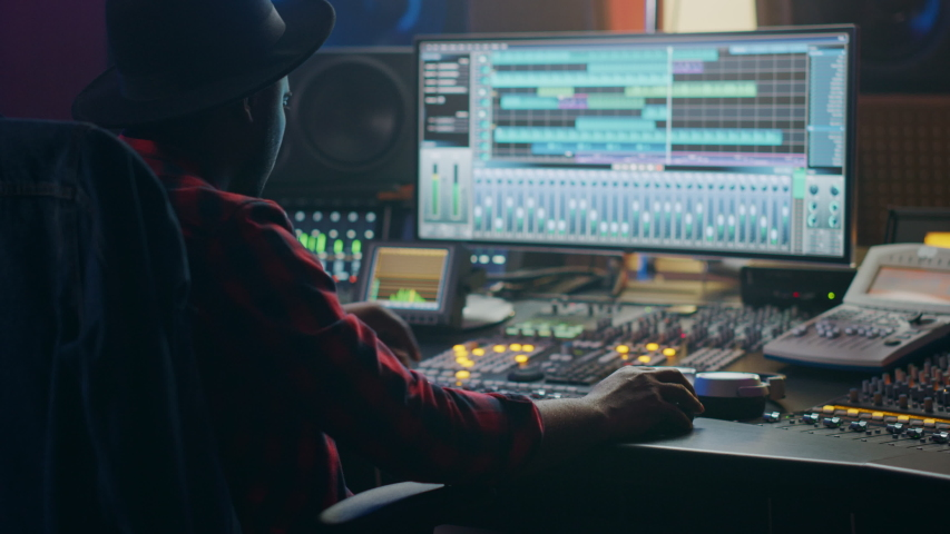 Audio Engineer, Music Creator, Musician, Artist Works in the Music Record Studio, Uses Surface Control Desk Equalizer Mixer. Buttons, Faders, Sliders to Broadcast, Record, Play Hit Song. Close-up Zoom Royalty-Free Stock Footage #1053781697