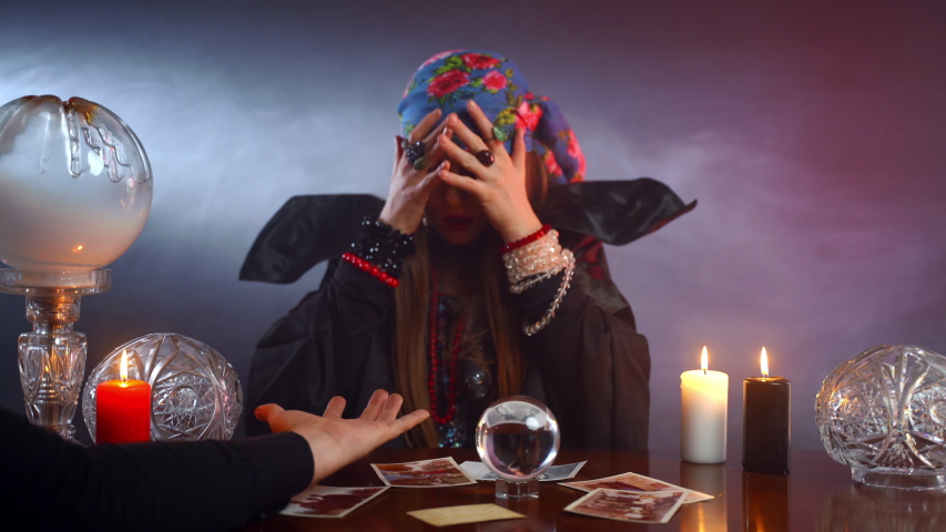 Generic fortune teller giving a helping hand to man, gypsy holding man's hand and reading fortune lines. Scared witch closing her face with hands after received information. Chiromancy and esoteric | Shutterstock HD Video #1053783902