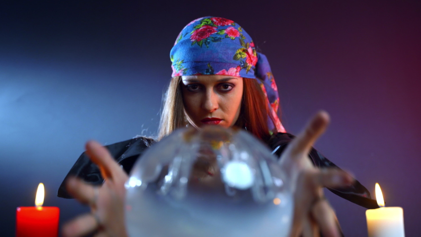 Female fortune teller moving hands above the magic crystal ball and spelling over it searching missing person, witch calling spirits to talk, person's fate in sorcerer's hands. Connection with | Shutterstock HD Video #1053783989