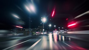 Driving fast on the German Autobahn and through a town at night, dynamic time lapse video with motion blur